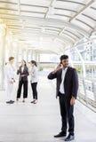 Fala com amigos Homem de negócio considerável que fala no telefone celular e que sorri com sua conversa dos amigos Imagem de Stock Royalty Free