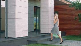 Fala da mulher elegante móvel perto da casa luxuosa Mulher bonita que vai com sacos vídeos de arquivo