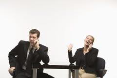 Fala de assento do homem de negócios e da mulher em telefones de pilha. Imagens de Stock