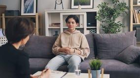 Fala de sorriso do adolescente emocional ao psychotherapist durante a sessão na clínica vídeos de arquivo