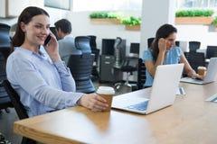 Fala executiva fêmea no telefone ao guardar a caneca de café Imagens de Stock Royalty Free