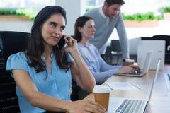 Fala executiva fêmea no telefone ao guardar a caneca de café Fotografia de Stock
