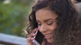Fala fêmea atrativa nova com seu amigo sobre o telefone celular, close up video estoque