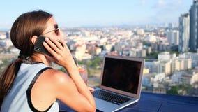 Fala fêmea no telefone ao trabalhar em um computador em um café do telhado com uma vista panorâmica de Pattaya filme