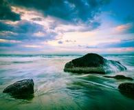 Fala i skały na plaży zmierzch Zdjęcie Stock
