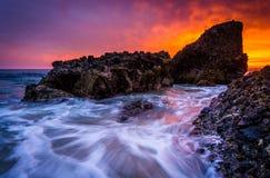 Fala i skały w Pacyficznym oceanie przy zmierzchem, przy drewno zatoczką Fotografia Royalty Free