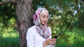A fala muçulmana nova e moderna da mulher comunica-se pelo telefone celular com os amigos video estoque