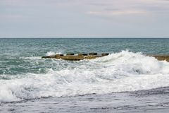 Fala na morzu blisko mola chmurzącego Fotografia Stock