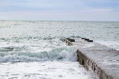 Fala na morzu blisko mola chmurzącego Obrazy Royalty Free