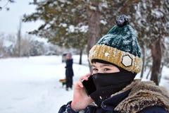 Fala no menino do telefone em um chapéu feito malha com um bubão e um passa-montanhas imagens de stock royalty free