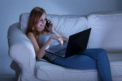 Fala no telefone e utilização do portátil Foto de Stock Royalty Free