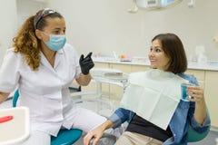 Fala paciente fêmea a um dentista no escritório dental Conceito da medicina, da odontologia e dos cuidados médicos imagem de stock