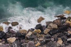 Fala rozbija na kolorowej skalistej plaży w Vernazza, Cinque Terre zdjęcia stock