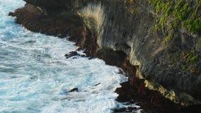 Fala uderza skały na tropikalnej plaży tworzy pluśnięcie kształt Potężne fala na skalistej plaży Sławna Uluwatu świątynia zbiory wideo