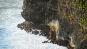 Fala uderza skały na tropikalnej plaży tworzy pluśnięcie kształt Potężne fala na skalistej plaży Sławna Uluwatu świątynia zbiory
