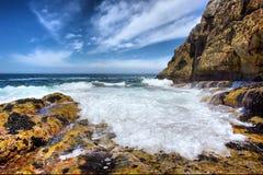 Fala z pianą biega na skalistej plaży fotografia royalty free