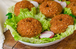 Falafel balls with lettuce on plate on wooden background. Selective focus Royalty Free Stock Photography