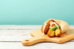 Falafel balls in pita with tahini sauce on wooden board Royalty Free Stock Images