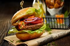 Falafel burger with addition of lettuce, tomato, onion, pickle cucumbers, spicy aromatic sauce and herbs on a wooden rustic table. stock images