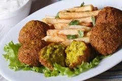 Falafel con le patate fritte su un piatto e su un tzatziki bianchi immagini stock libere da diritti