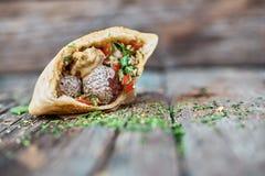 Falafel en verse groenten in pitabroodje op houten lijst Gezonde Levensstijl Selectieve nadruk Stock Fotografie