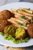 Falafel with French fries, salad on the white plate vertical Royalty Free Stock Images