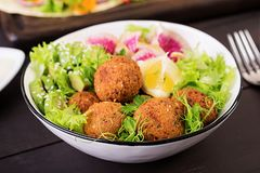 Falafel and fresh vegetables. Buddha bowl. Middle eastern or arabic dishes. On a dark background. Halal food stock photos