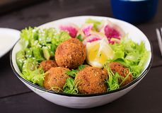 Falafel and fresh vegetables. Buddha bowl. Middle eastern or arabic dishes. On a dark background. Halal food stock images