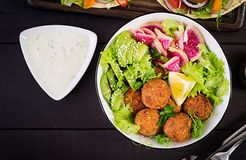 Falafel and fresh vegetables. Buddha bowl. Middle eastern or arabic dishes. On a dark background. Halal food. Top view. Copy space stock photography