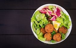 Falafel and fresh vegetables. Buddha bowl. Middle eastern or arabic dishes. On a dark background. Halal food. Top view. Copy space stock image