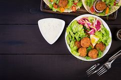 Falafel and fresh vegetables. Buddha bowl. Middle eastern or arabic dishes. On a dark background. Halal food. Top view. Copy space stock images