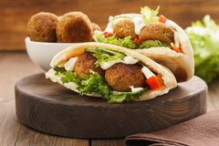 Falafel and fresh vegetables in pita bread with sauce royalty free stock photo