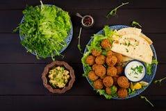 Falafel, hummus и пита Ближневосточные или арабские блюда на темной предпосылке стоковое фото