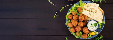 Falafel, hummus and pita. Middle eastern or arabic dishes on a dark background. Halal food. Top view. Banner stock images