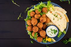 Falafel, hummus and pita. Middle eastern or arabic dishes on a dark background. Halal food. Top view. Copy space stock photography