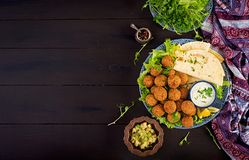 Falafel, hummus and pita. Middle eastern or arabic dishes on a dark background. Halal food. Top view. Copy space royalty free stock photo