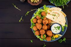 Falafel, hummus and pita. Middle eastern or arabic dishes on a dark background. Halal food. Top view. Copy space royalty free stock photos