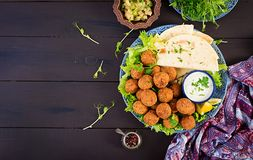 Falafel, hummus and pita. Middle eastern or arabic dishes on a dark background. Halal food. Top view. Copy space stock image