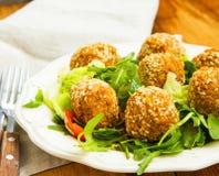 falafel Kekersballen met sesam en groene salade op plaat Royalty-vrije Stock Fotografie