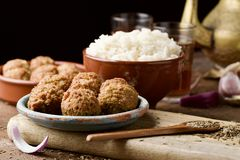 Falafel and long grain rice on a wooden table. Some falafel in a green earthenware plate and a brown earthenware bowl with long grain rice on a rustic wooden royalty free stock images