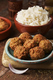 Falafel and long grain rice on a wooden table. Some falafel in a green earthenware plate and a brown earthenware bowl with long grain rice on a rustic wooden Royalty Free Stock Image