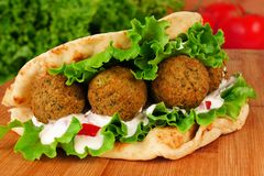 Falafel pita wrap. Falafel with vegetables and  tzatziki sauce in pita bread close-up on wooden table Stock Photos