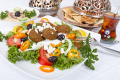 Falafel Salad with Pita and Hummus. Falafel Salad with Pita Bread and Hummus plate, complimented with tea on a white table cloth Royalty Free Stock Image