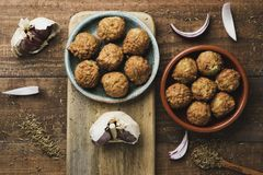 Falafel in some earthenware plates. High angle view of some falafel served in two different earthenware plates placed on a rustic wooden table royalty free stock photos