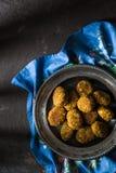 Falafel végétarien d'un fer-blanc sur un espace libre bleu de serviette Photographie stock