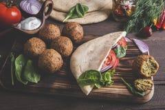 Falafel, verse groenten, saus en pitabroodje op houten lijst royalty-vrije stock fotografie
