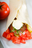 Falafel wrap. Fresh traditional falafel wrap on pita bread with fresh chopped tomatoes Royalty Free Stock Photography