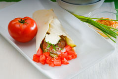 Falafel wrap. Fresh traditional falafel wrap on pita bread with fresh chopped tomatoes Royalty Free Stock Image