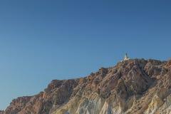 Falaise avec le phare en haut dans Santorini Photo stock