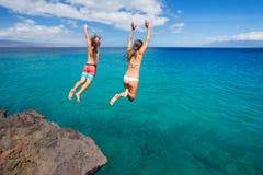 Falaise d'amis sautant dans l'océan Photos libres de droits
